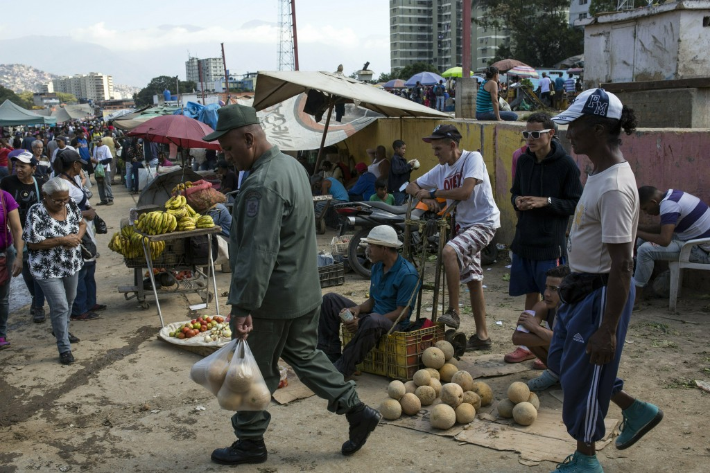 Workers and customers gather at a wholesale food market in Caracas, Venezuela, Monday, Jan. 28, 2019. Economists agree that the longer the standoff be...