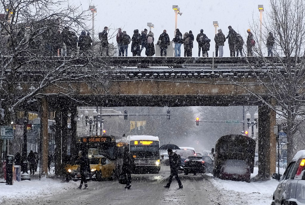 Commuters wait for a train as snow falls Monday, Jan. 28, 2019, in Chicago. The plunging temperatures expected later this week that have forecasters e...