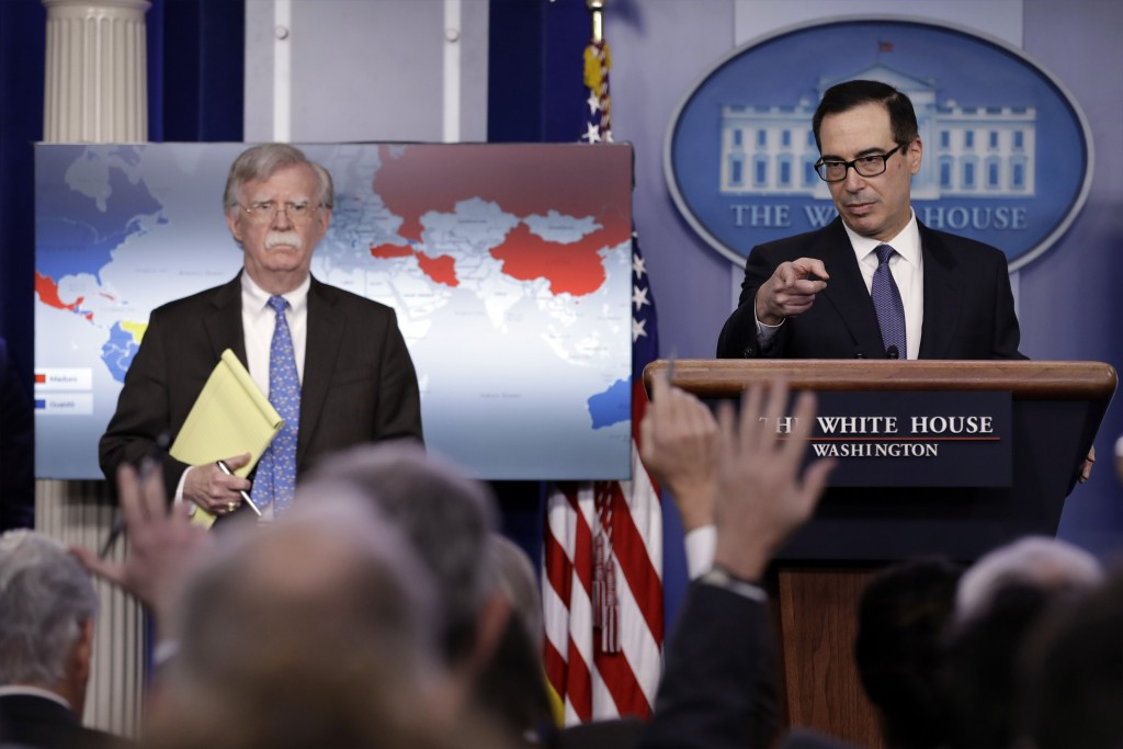 National security adviser John Bolton listens as Treasury Secretary Steven Mnuchin takes questions from reporters during a press briefing at the White