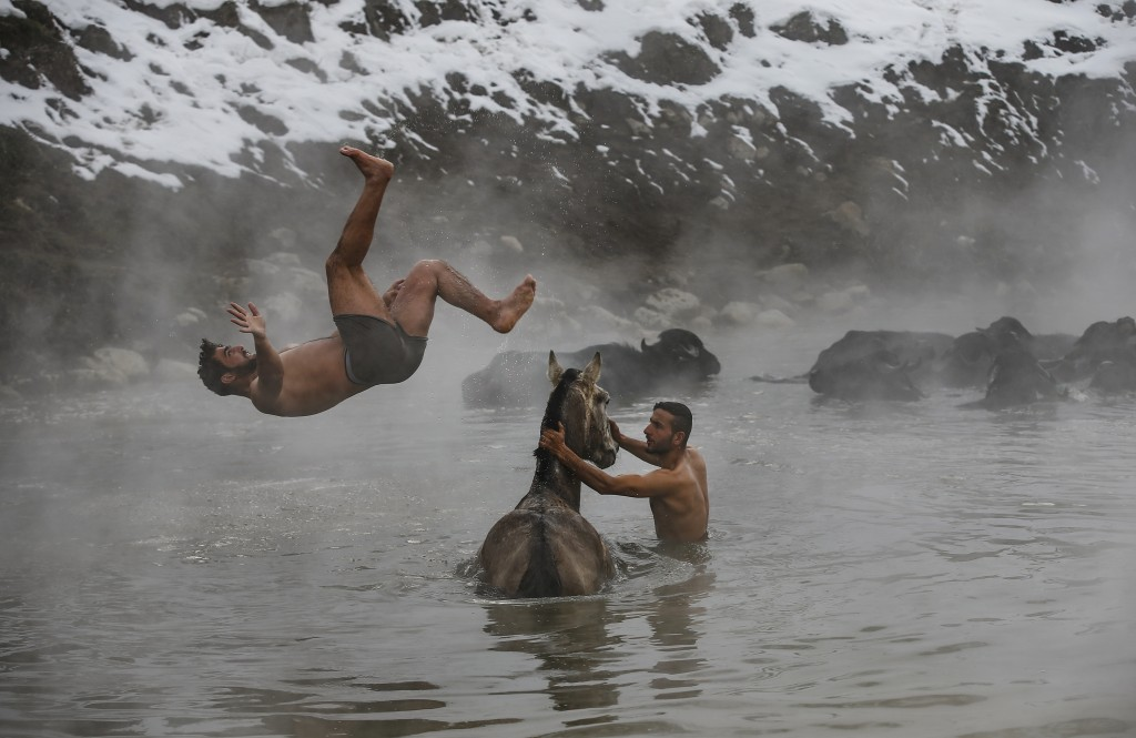 In this Thursday, Jan. 24, 2019 photo, Muhammed Toren, 18, left, and Berkan Toren, 20, enjoy a hot spring along with their water buffaloes near the vi