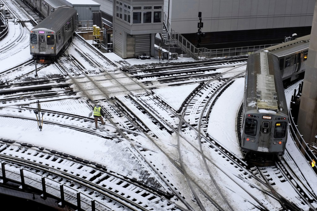 Chicago's El trains move along snow-covered tracks Monday, Jan. 28, 2019, in Chicago. The plunging temperatures expected later this week that have for...
