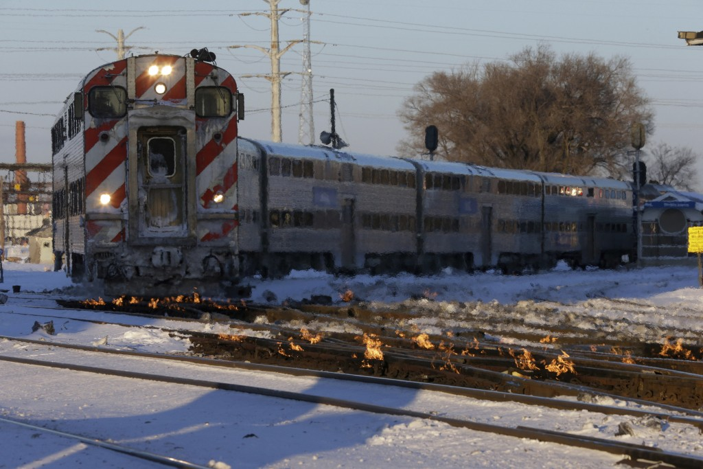 A Metra train moves southbound to downtown Chicago as the gas-fired switch heater on the rails keeps the ice and snow off the switches near Metra West