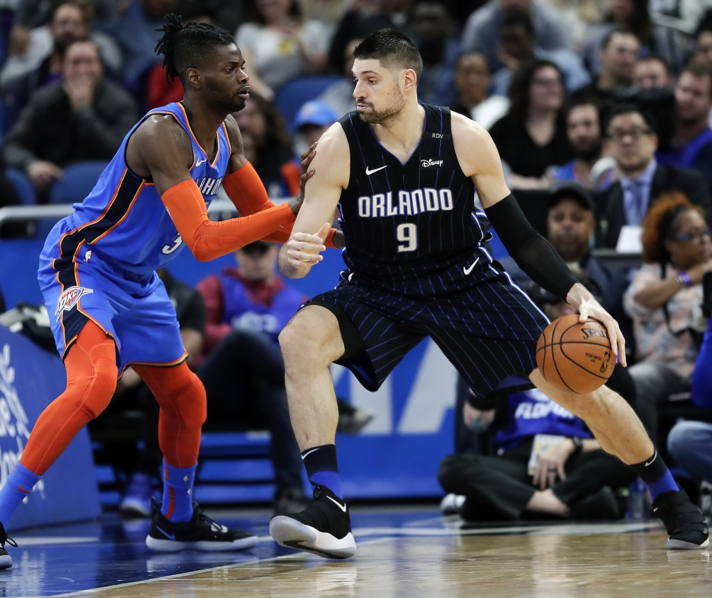 Orlando Magic's Nikola Vucevic (9) goes to the basket against Oklahoma City Thunder's Nerlens Noel, left, during the first half of an NBA basketball g...