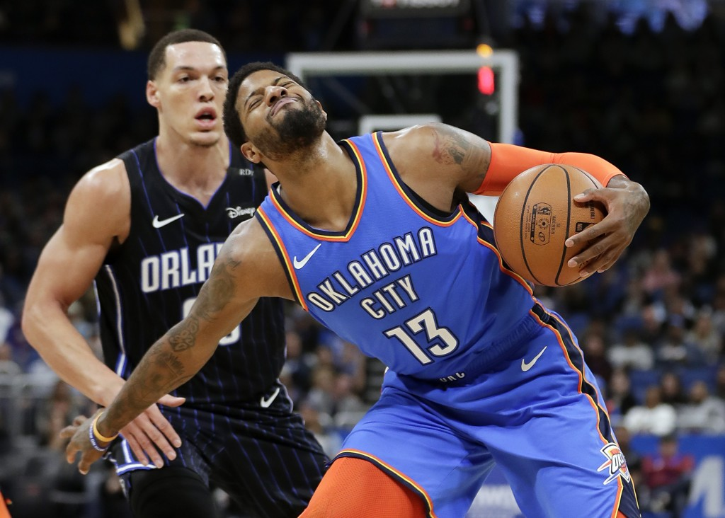 Oklahoma City Thunder's Paul George (13) grimaces after he is fouled by Orlando Magic's Aaron Gordon, left, during the first half of an NBA basketball...