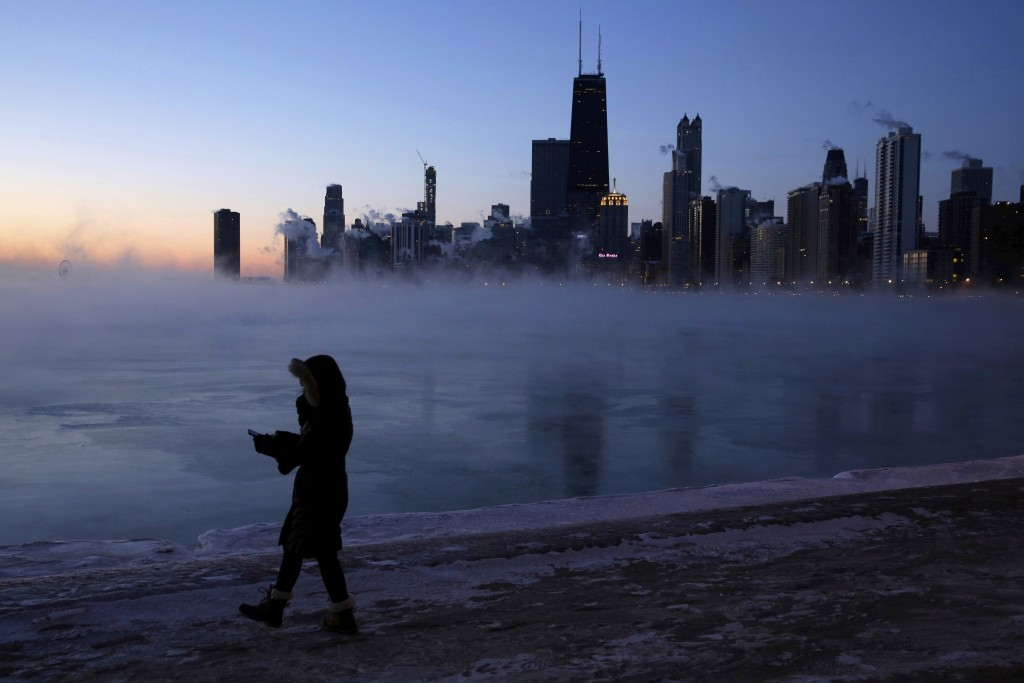 A person walks along the lakeshore, Wednesday, Jan. 30, 2019, in Chicago. A deadly arctic deep freeze enveloped the Midwest with record-breaking tempe