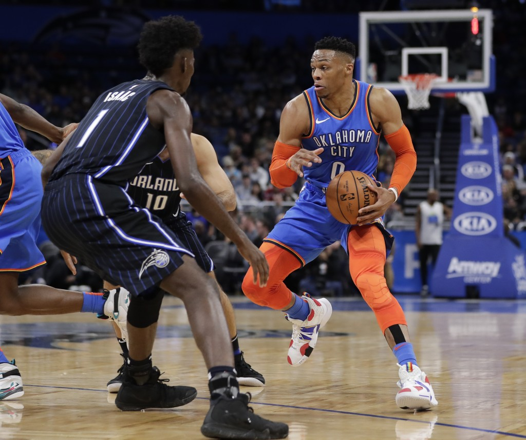 Oklahoma City Thunder's Russell Westbrook, right, looks for a way around Orlando Magic's Jonathan Isaac (1) during the first half of an NBA basketball...