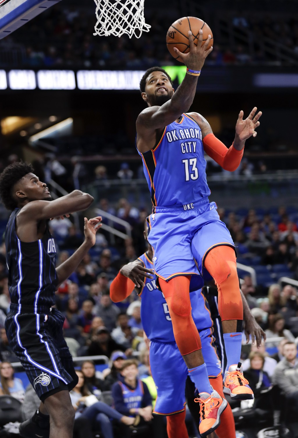 Oklahoma City Thunder's Paul George (13) goes past Orlando Magic's Jonathan Isaac, left, for a basket during the first half of an NBA basketball game,...