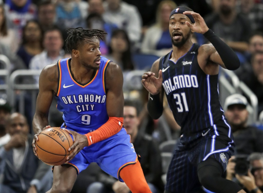 Oklahoma City Thunder's Jerami Grant (9) looks to pass as he is defended by Orlando Magic's Terrence Ross (31) during the second half of an NBA basket...