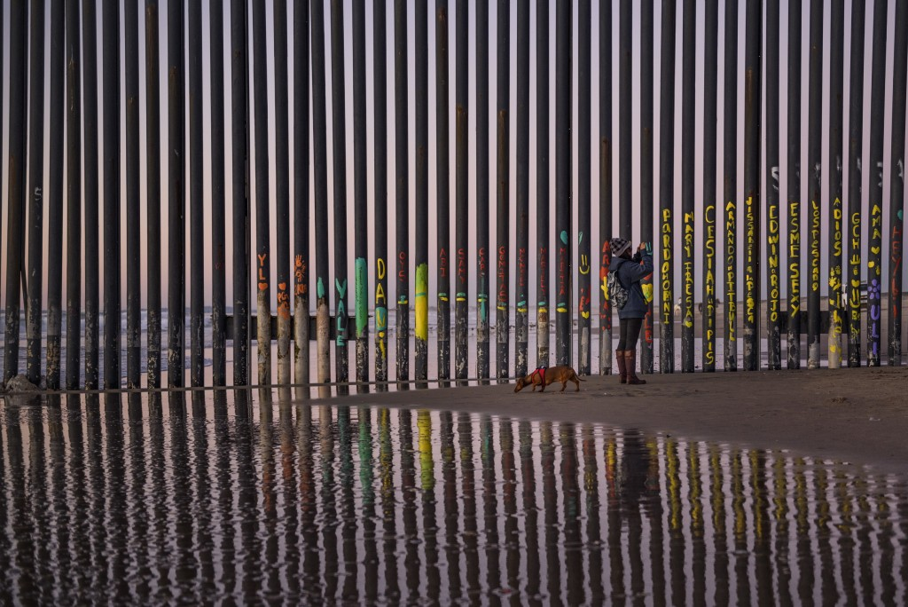 FILE - In this Jan. 3, 2019, file photo, a woman takes a photo by the border fence between San Diego, Calif., and Tijuana, as seen from Mexico. The to...