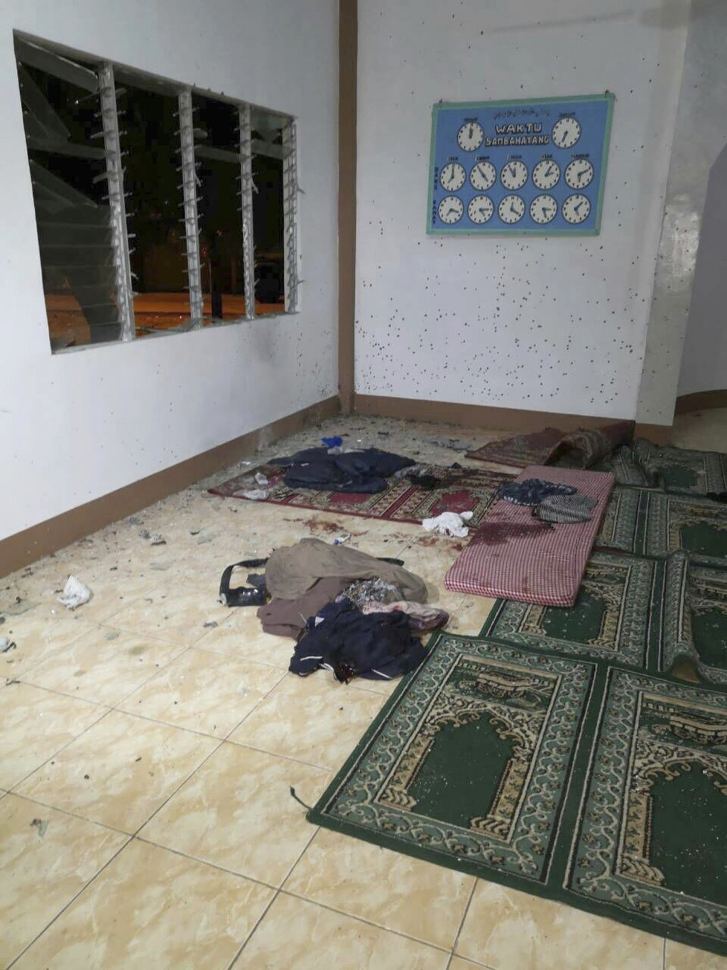 In this photo provided by WESMINCOM Armed Forces of the Philippines, blood-stained clothes and prayer mats are seen inside a Muslim Mosque following a...