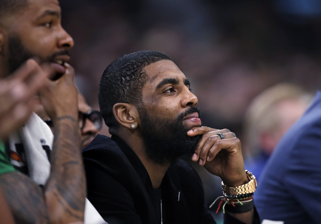 Boston Celtics guard Kyrie Irving, center, who is sidelined with a hip strain, watches play from the bench with forward Marcus Morris, left, during th...