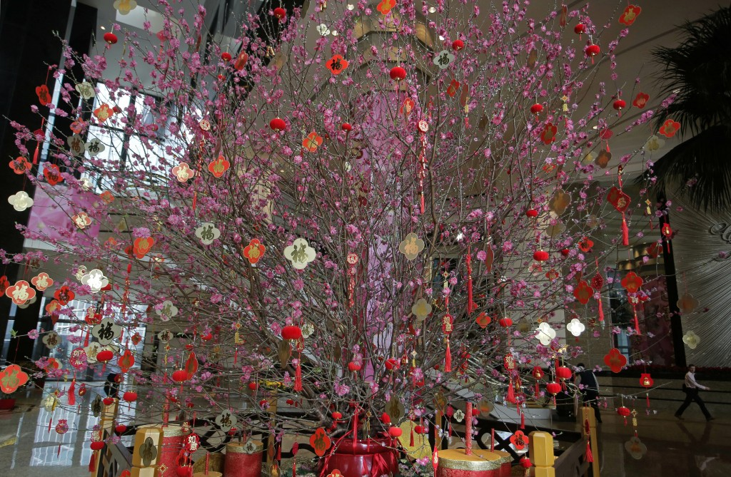 A huge peach blossom is displayed as Chinese New Year decorations at an office building in Hong Kong, Thursday, Jan. 31, 2019. Chinese will celebrate