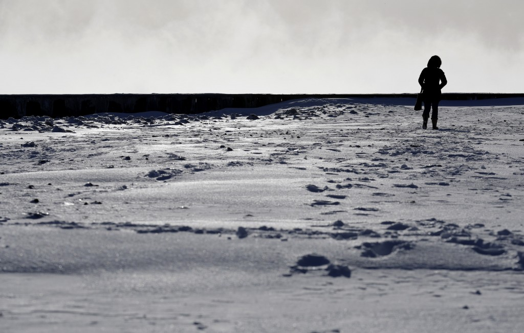 A woman walks along the shore of Lake Michigan at the Lighthouse Park in Evanston, Ill., Wednesday, Jan. 30, 2019. A deadly arctic deep freeze envelop