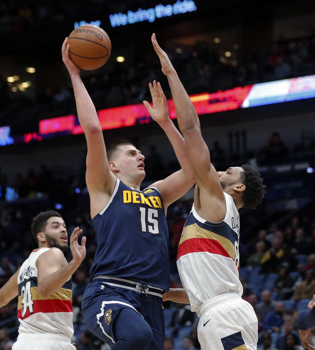 Denver Nuggets center Nikola Jokic (15) goes to the basket against New Orleans Pelicans center Jahlil Okafor in the first half of an NBA basketball ga...