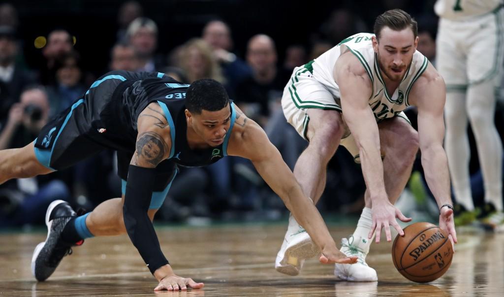 Charlotte Hornets forward Miles Bridges, left, dives as Boston Celtics forward Gordon Hayward, right, grabs a loose ball during the second half of an ...