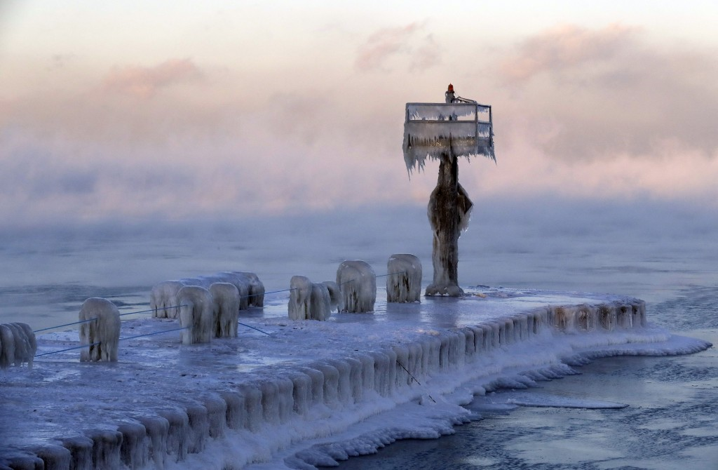 A harbor light is covered by snow and ice on the Lake Michigan at 39th Street Harbor, Wednesday, Jan. 30, 2019, in Chicago. A deadly arctic deep freez...