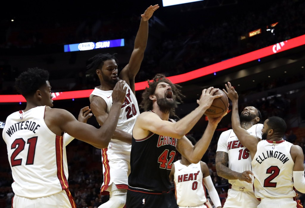 Chicago Bulls center Robin Lopez (42) is fouled by Miami Heat forward Justise Winslow (20) during the first half of an NBA basketball game, Wednesday,...