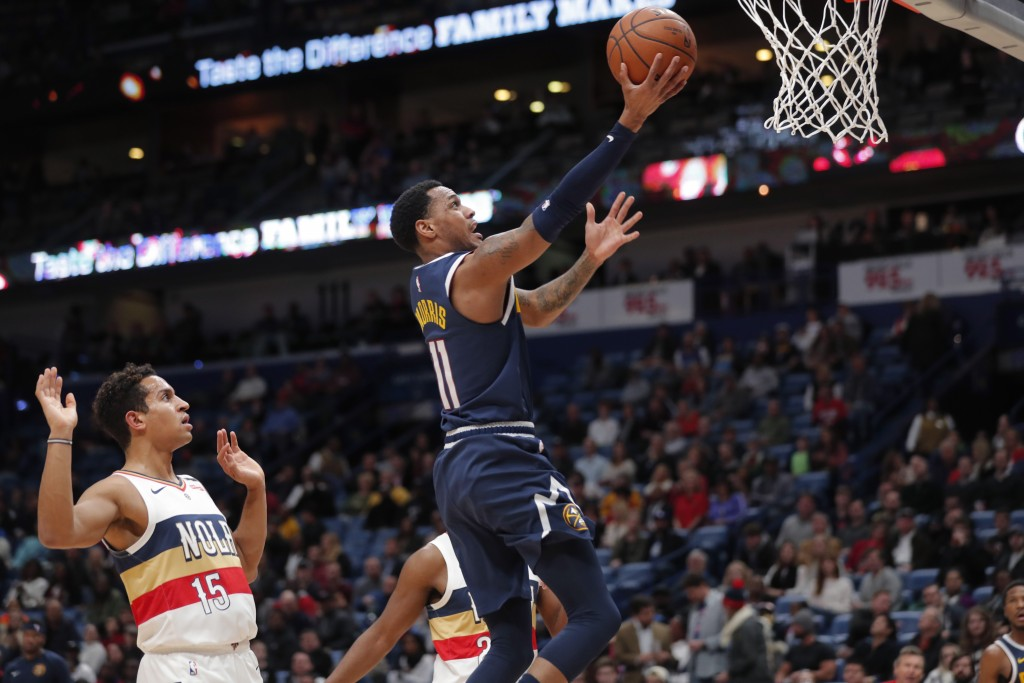 Denver Nuggets guard Monte Morris (11) goes to the basket in front of New Orleans Pelicans guard Frank Jackson (15) during the first half of an NBA ba...