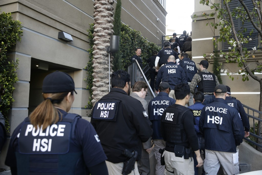 FILE - In this March 3, 2015 file photo, federal agents enter an upscale apartment complex where authorities say a birth tourism business charged preg...