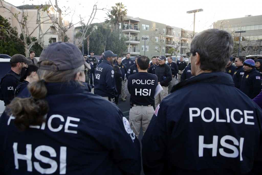 FILE - In this March 3, 2015 file photo, federal agents gather at a nearby parking lot before raiding an upscale apartment complex where authorities s...