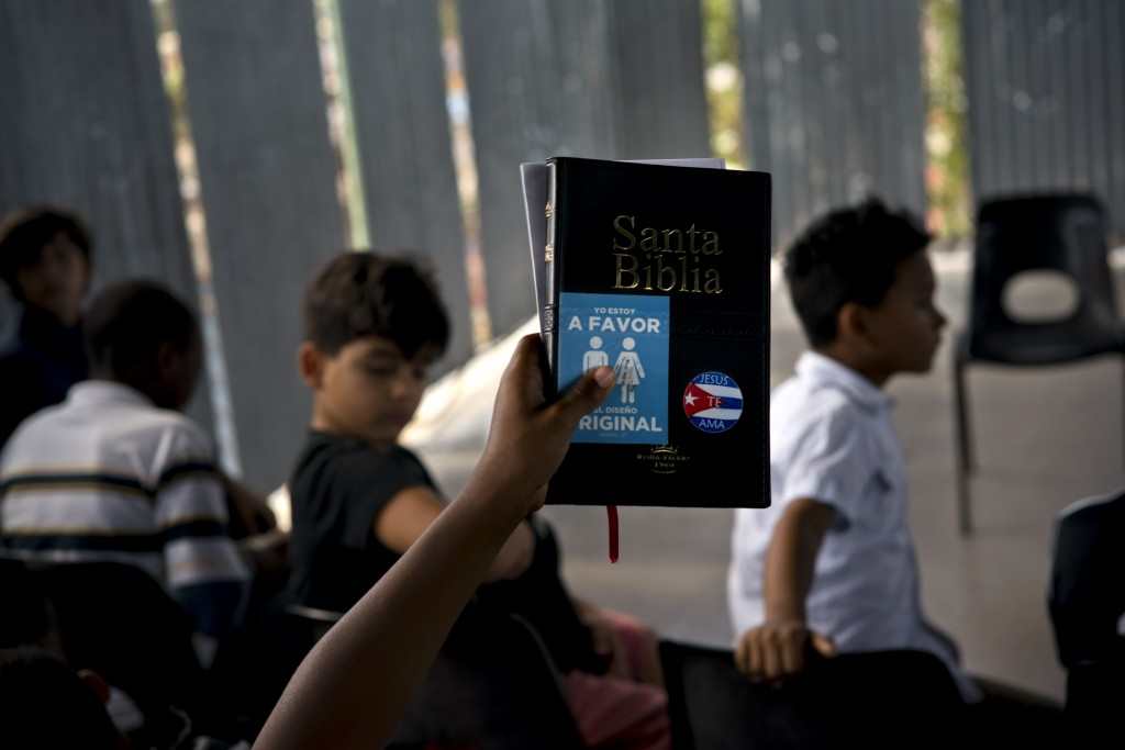 """A child holds up a bible with a sticker that reads """"I am in favor of the original design """" during bible school at an evangelical church in Havana, Cub..."""