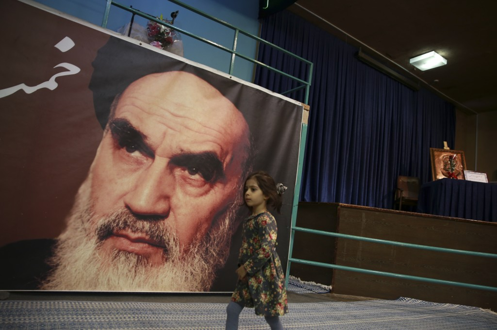 In this Tuesday, Jan. 22, 2019, photo, a girl walks past a poster of Ayatollah Ruhollah Khomeini, at a mosque where he made speeches, in northern Tehr