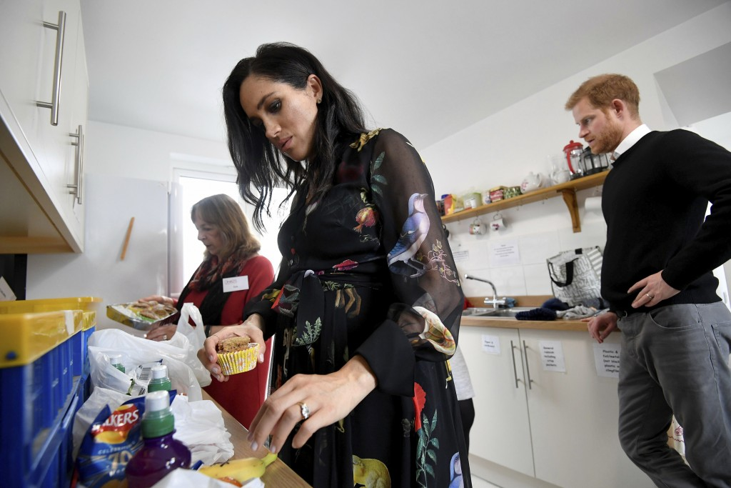 Britain's Prince Harry, behind, looks on as Meghan, Duchess of Sussex helps prepare food parcels during her visit to the One25 charity kitchen in Bris...