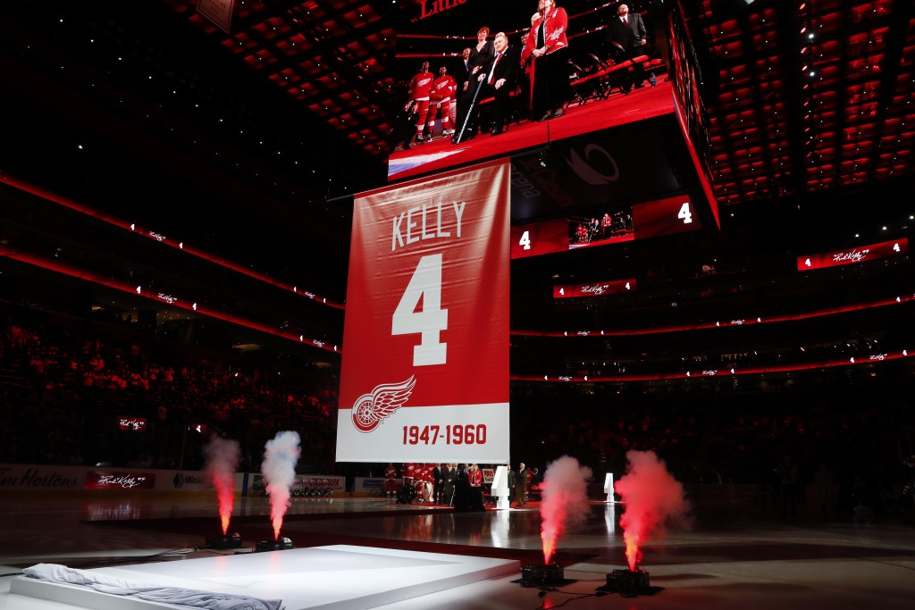 Former Detroit Red Wings player Red Kelly, displayed on the video board, watches during his jersey retirement ceremony before an NHL hockey game again...