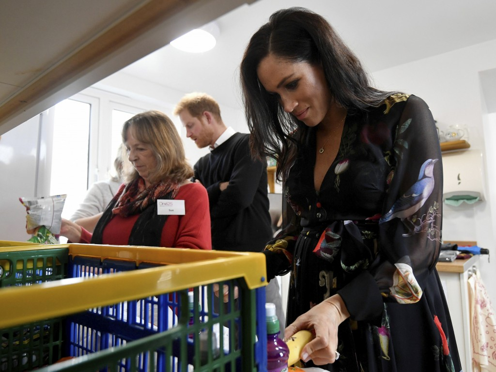 Britain's Prince Harry, behind, looks on as Meghan, Duchess of Sussex helps prepare personalised messages on fruit during her visit to the One25 chari...