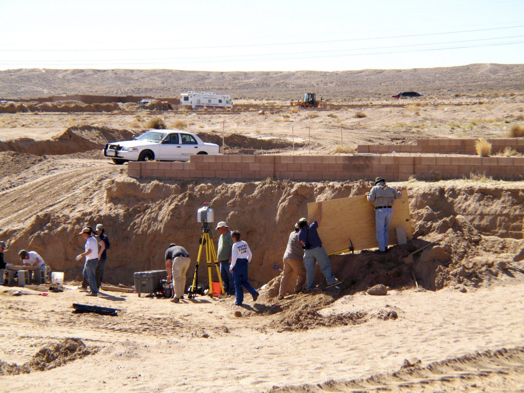 FILE - In this Feb. 28, 2009 file photo, forensic experts excavate human remains from an area that had been razed for a housing development in Albuque