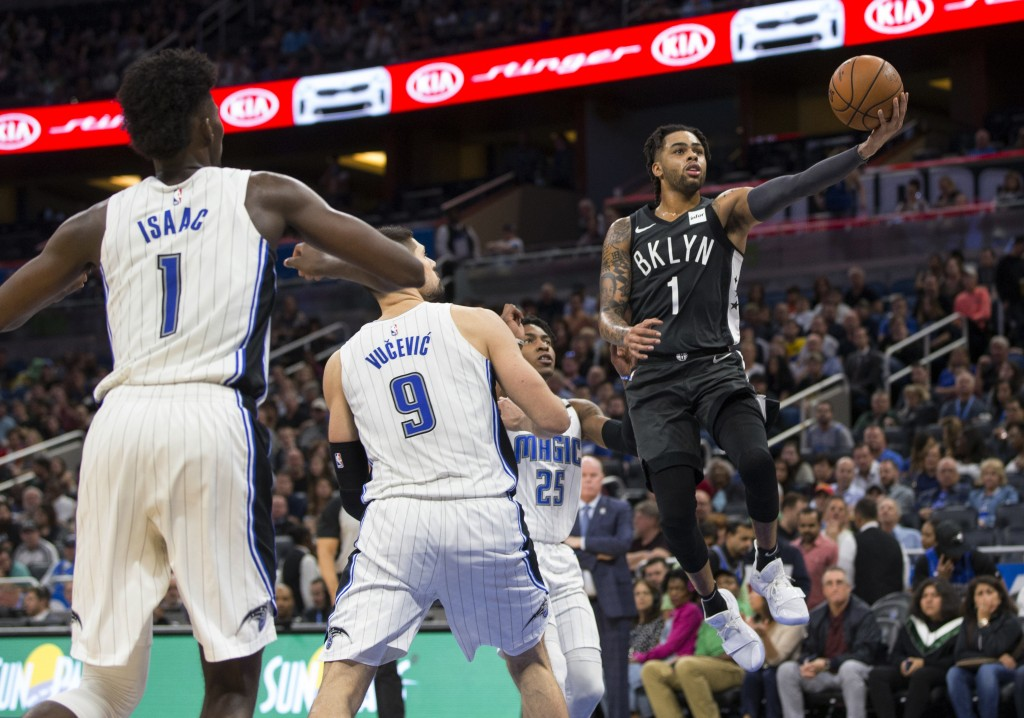 Brooklyn Nets guard D'Angelo Russell (1) lays the ball up in front of Orlando Magic forward Jonathan Isaac (1) and center Nikola Vucevic (9) during th...