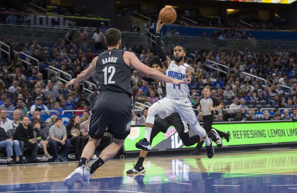 Orlando Magic guard D.J. Augustin (14) passes the ball while defended by Brooklyn Nets forward Joe Harris (12) during the first half of an NBA basketb...