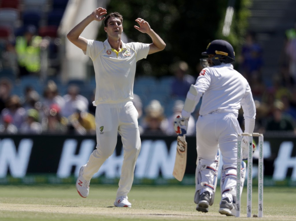 Australia's Pat Cummins, left, raises his arms after bowling to Sri Lanka's Dhananjaya de Silva, right, on day 3 of their cricket test match in Canber