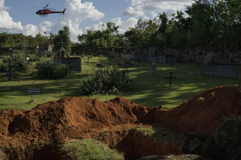 FILE - In this Jan. 28, 2019 file photo, a helicopter carrying a body pulled from the mud, days after a Vale dam collapsed, flies over a cemetery with...