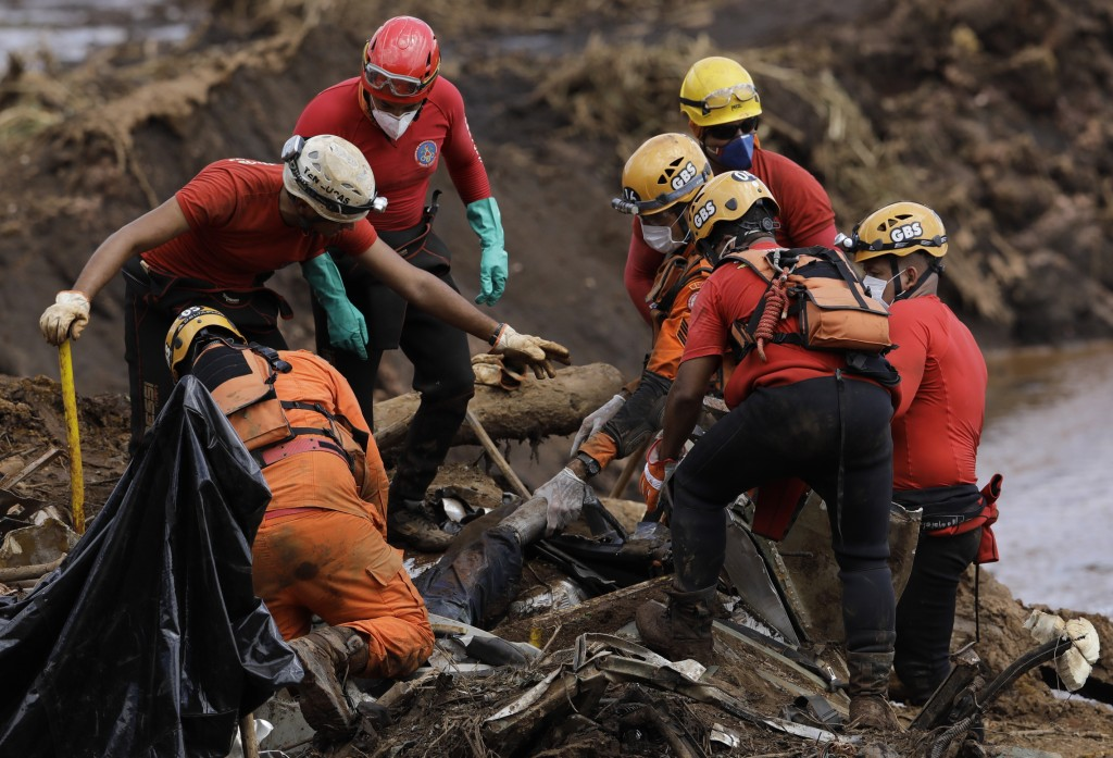 FILE - In this Jan. 28, 2019 file photo, firefighters pull a body from the mud days after the Vale mining company's dam collapsed in Brumadinho, Brazi...