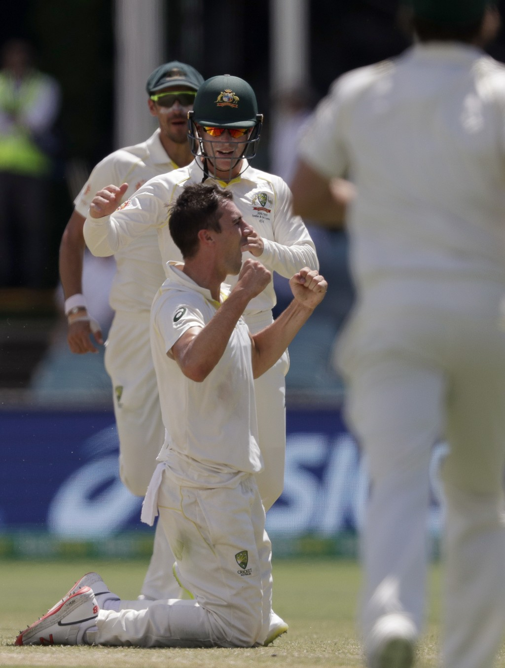 Australia's Pat Cummins, front left, celebrates his caught and bowled on Sri Lanka's Lahiru Thirimanne on day 4 of their cricket test match in Canberr...
