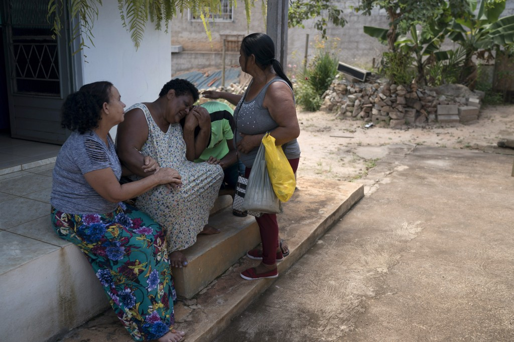 Malvina Firmina Nunes and her son Fernando are comforted by friends at their home as they grieve for their missing 35-year-old son and brother, Peters...