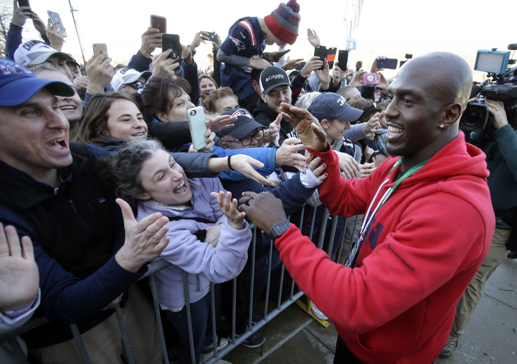 New England Patriots free safety Devin McCourty, right, greets fans following the football teams arrival at Gillette Stadium, Monday, Feb. 4, 2019, in
