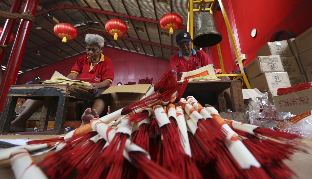 In this Monday, Jan. 28, 2019, photo, workers prepare for the Lunar New Year at the Dharma Bakti Temple in Chinatown area of Jakarta, Indonesia. Peopl
