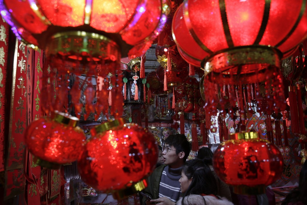 In this Tuesday, Jan. 29, 2019, photo, people shop for Lunar New Year decorations at a market in Beijing. (AP Photo/Andy Wong)