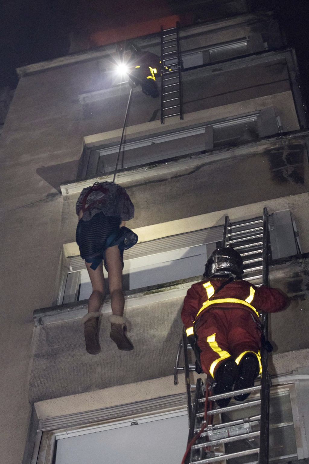 In this image provided on Tuesday, Feb. 5, 2019 by the Brigade de Sapeurs-Pompiers de Paris (Paris Fire Brigade) firefighters use a rope to evacuate a...