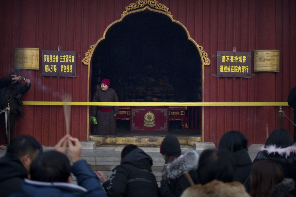 A monk watches as people pray at the Lama Temple in Beijing, Tuesday, Feb. 5, 2019. Chinese people are celebrating the first day of the Lunar New Year