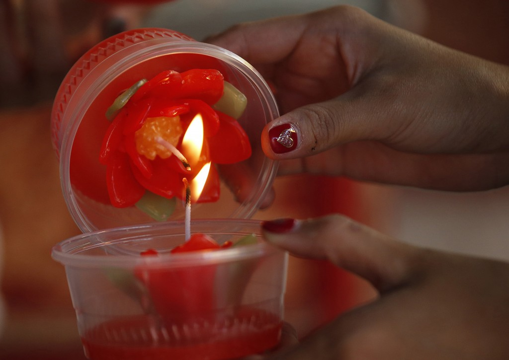 In this Wednesday, Jan. 30, 2019, photo, ethnic Chinese-Thai light candles after praying at the Leng Nuei Yee Chinese temple for the upcoming Lunar Ne