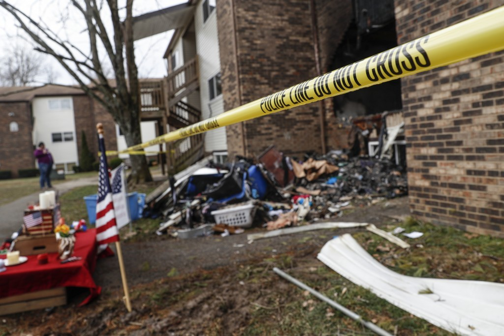 Police tape surrounds an apartment damaged by fire involved in a shooting incident that resulted in the death of a Clermont County Sheriff's Office De...