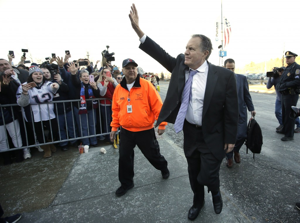 New England Patriots head coach Bill Belichick, center right, waves to fans following the football teams arrival at Gillette Stadium, Monday, Feb. 4,