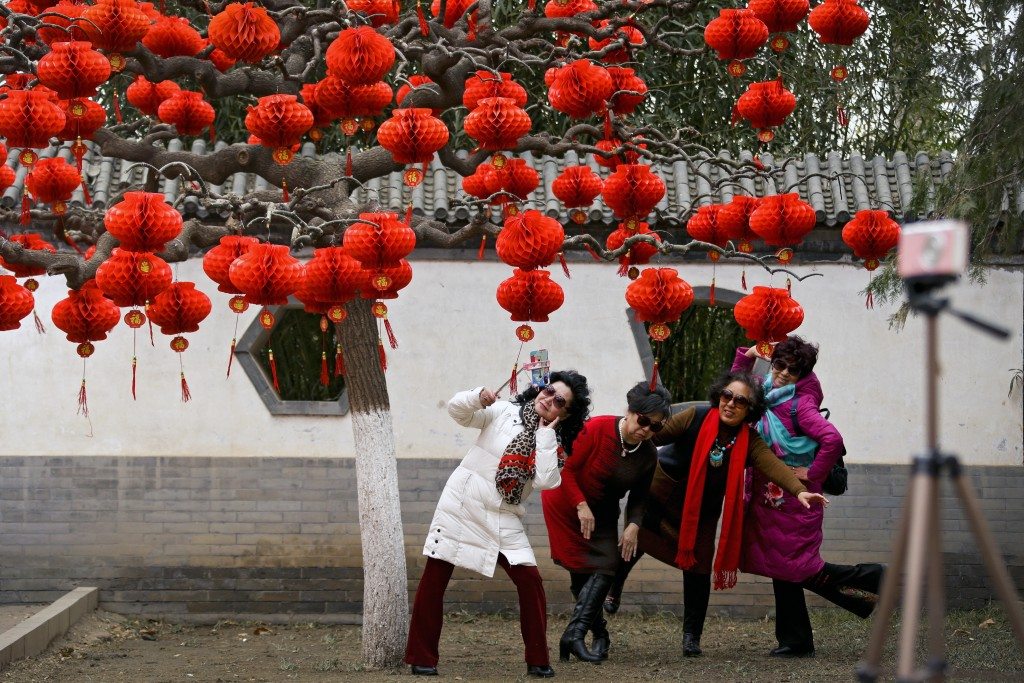 In this Wednesday, Jan. 30, 2019, photo, women take a selfie near a tree decorated with red lanterns ahead of the Lunar New Year at Ditan Park in Beij