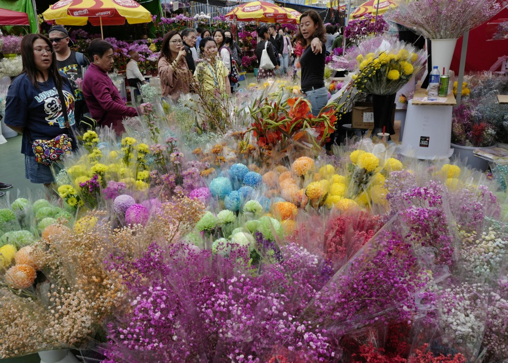 In this Monday, Feb. 4, 2019, photo, people buy flowers at a New Year market in Hong Kong's Victoria Park. Chinese will celebrate the lunar new year o