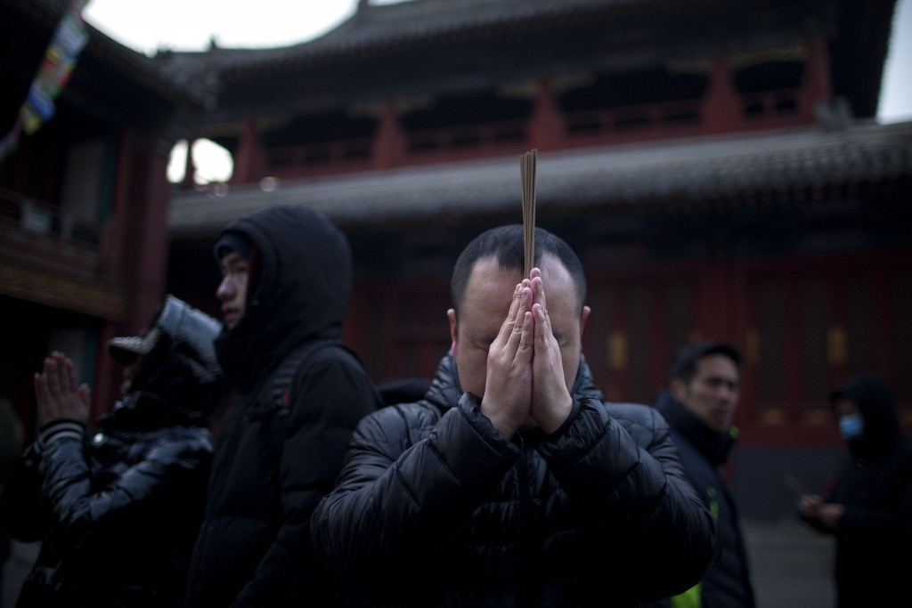 People hold sticks of incense as they pray at the Lama Temple in Beijing, Tuesday, Feb. 5, 2019. Chinese people are celebrating the first day of the L