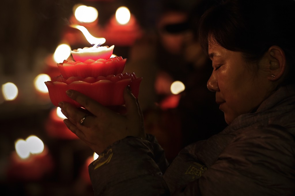 A woman holds a flower-shape candle prays on the first day of the Chinese Lunar New Year at the Tanzhe temple in the Mentougou District of Beijing, Tu
