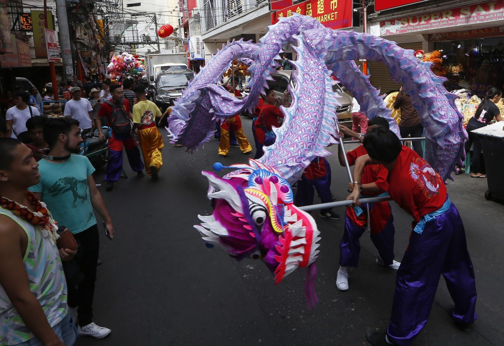 In this Monday, Feb. 4, 2019, photo, Filipino-Chinese perform a dragon dance on Chinese New Year's Eve at Manila's Chinatown district in Manila, Phili
